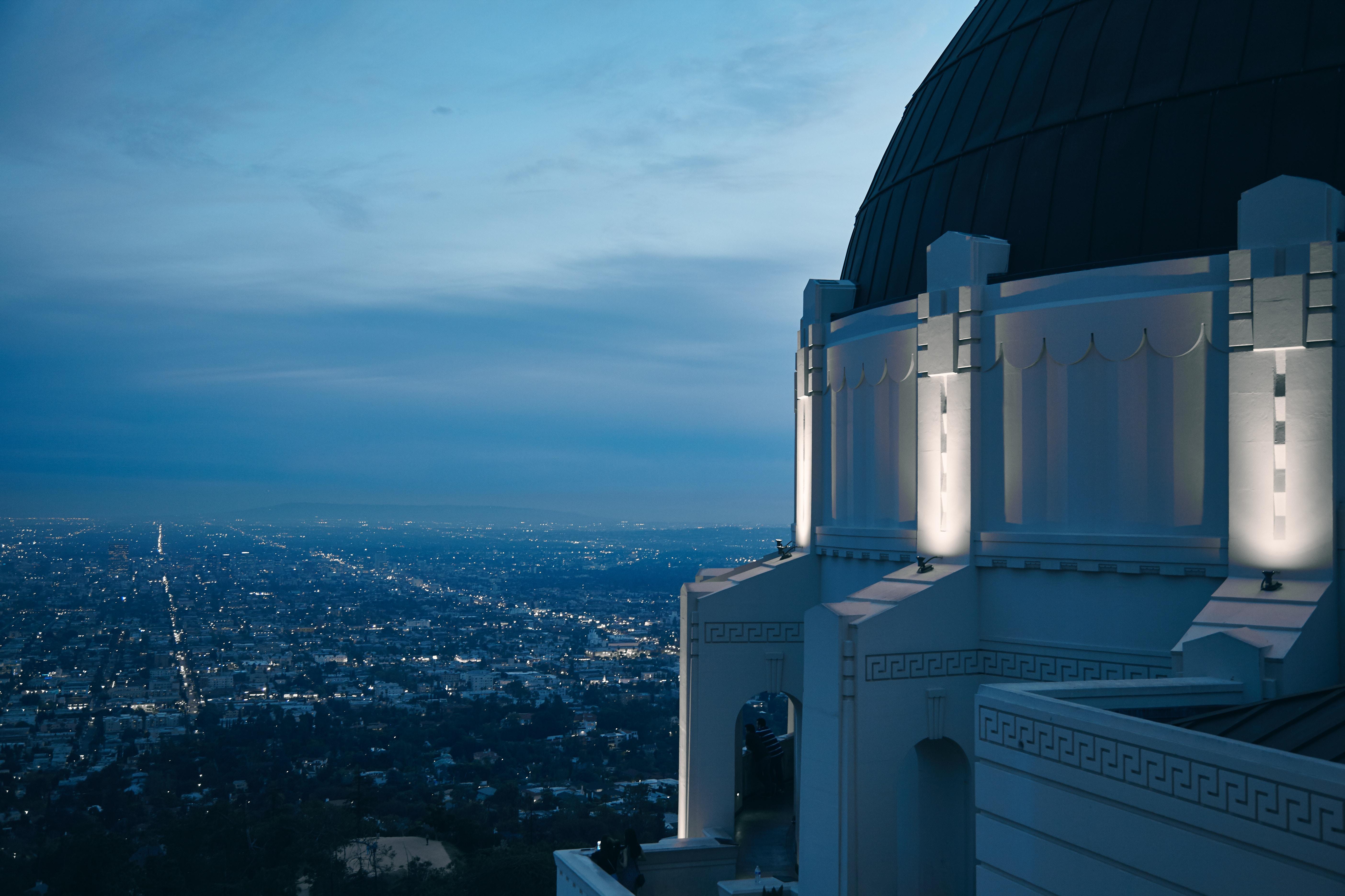 Griffith Observatory at dusk with a cityscape in the background